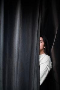 woman hiding behind black curtain