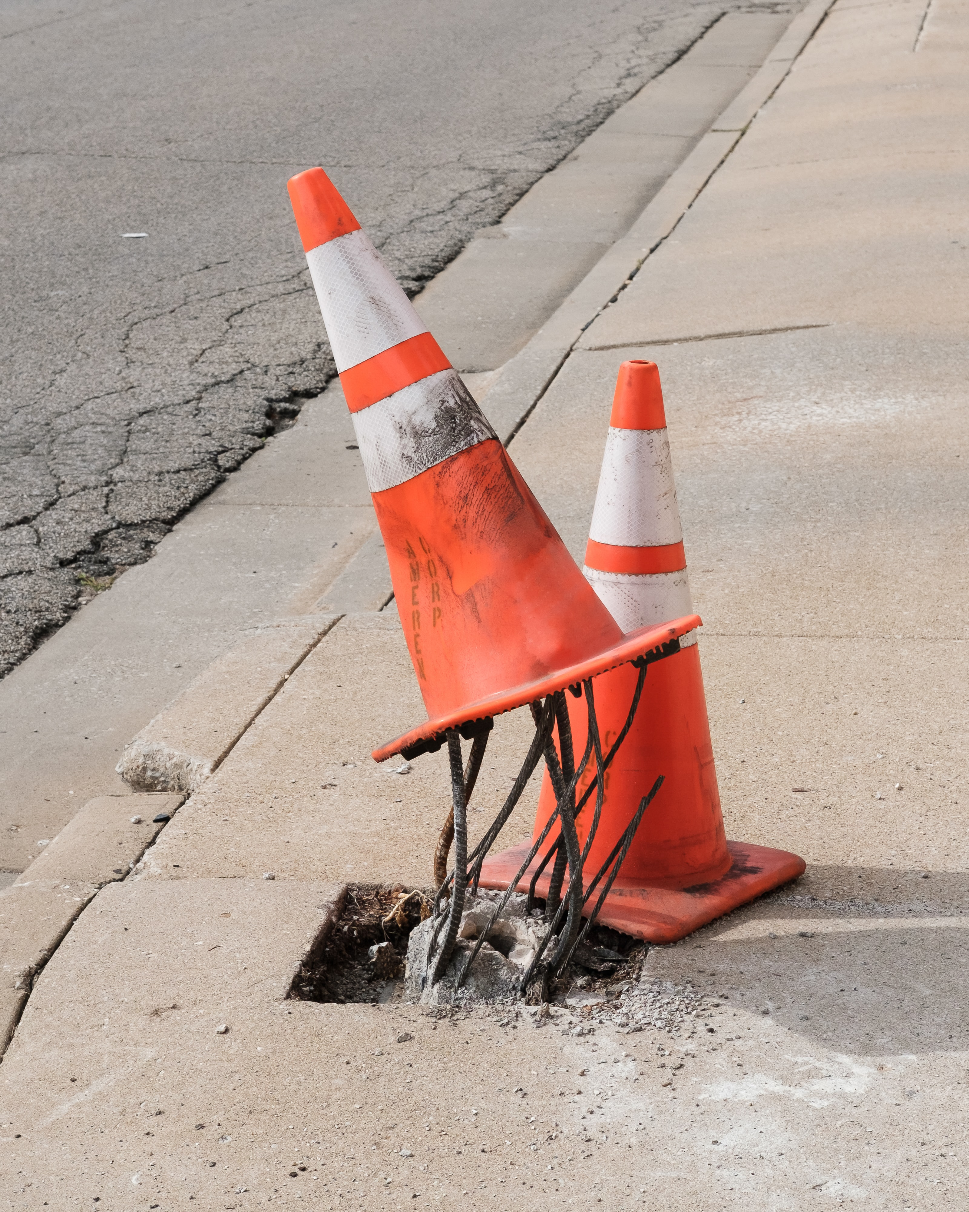 two traffic cones on gray road