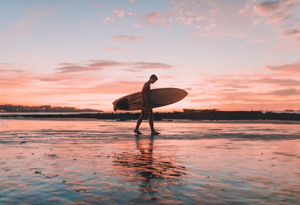 man holding surfboard walking near seashore