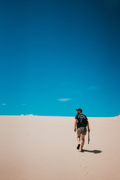 person walking on sand during day time
