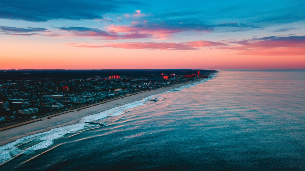 aerial photography of buildings near ocean during golden hour