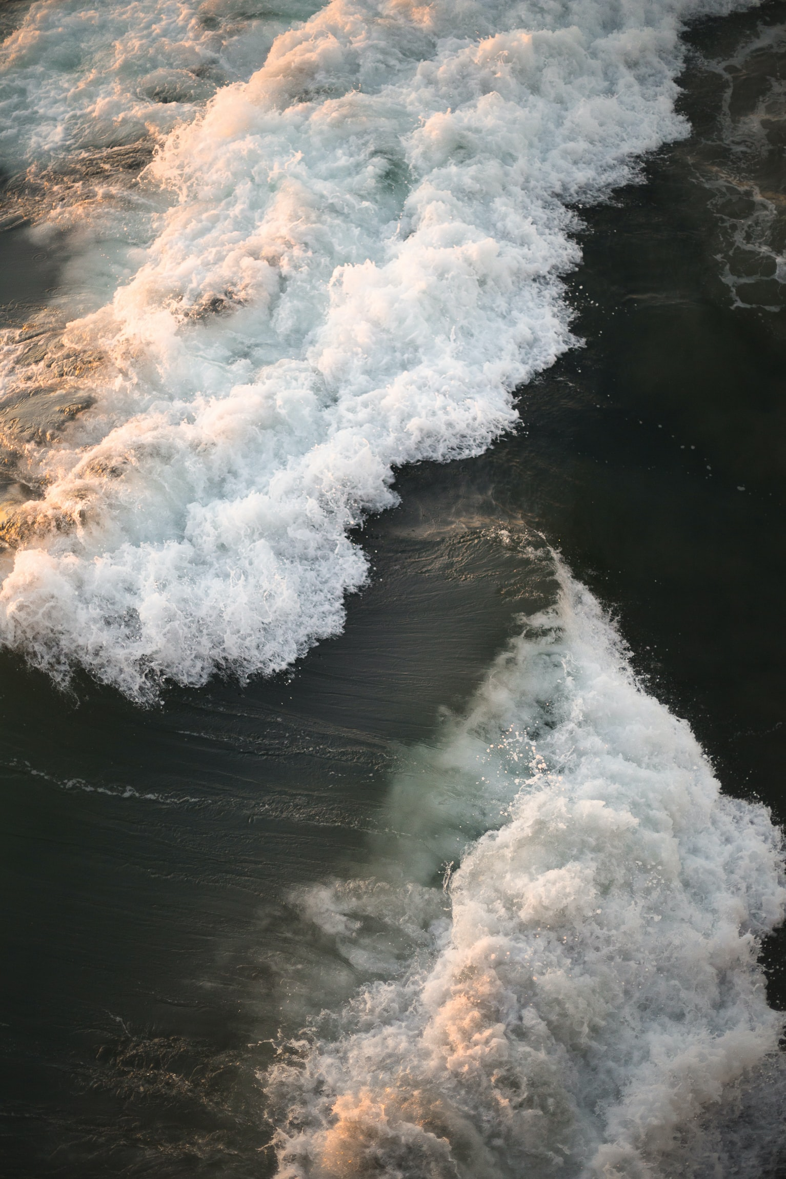 waves crashing on shore in aerial photography
