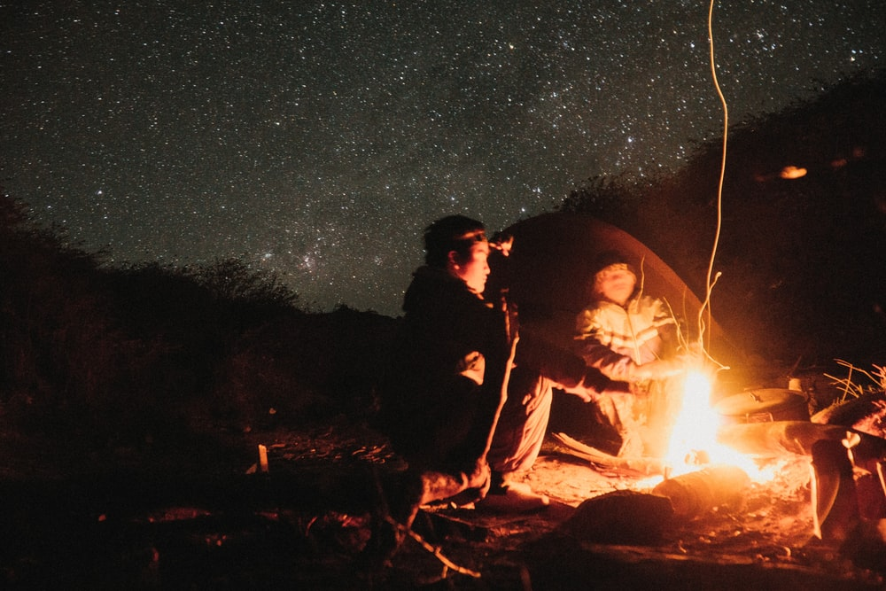 two persons lighting up campfier