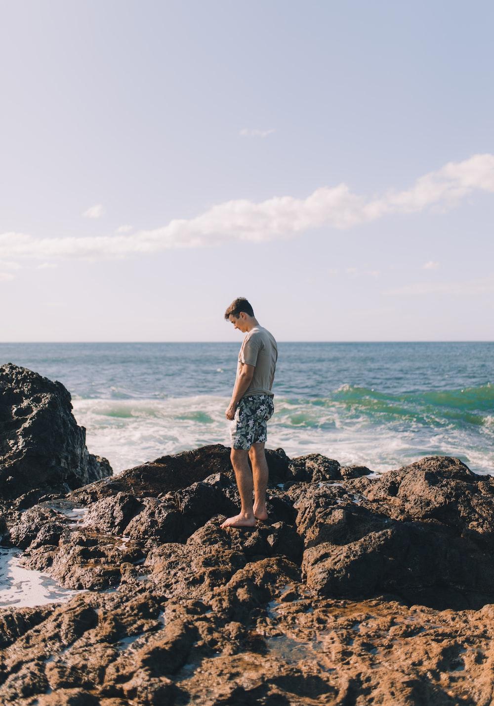 man standing on rock island beside beach