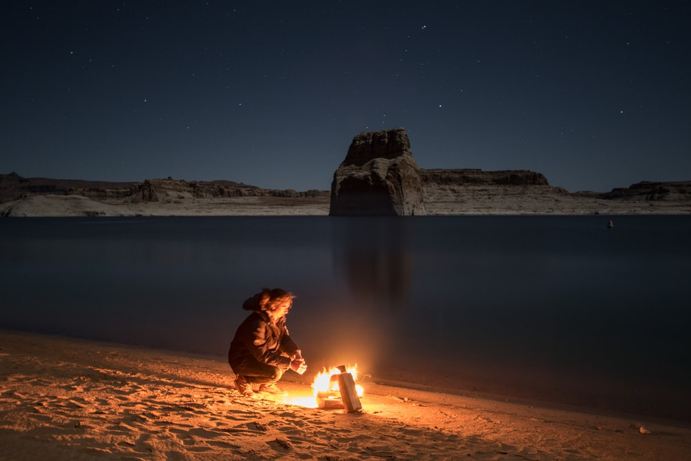 person sitting beside bonfire on seashore