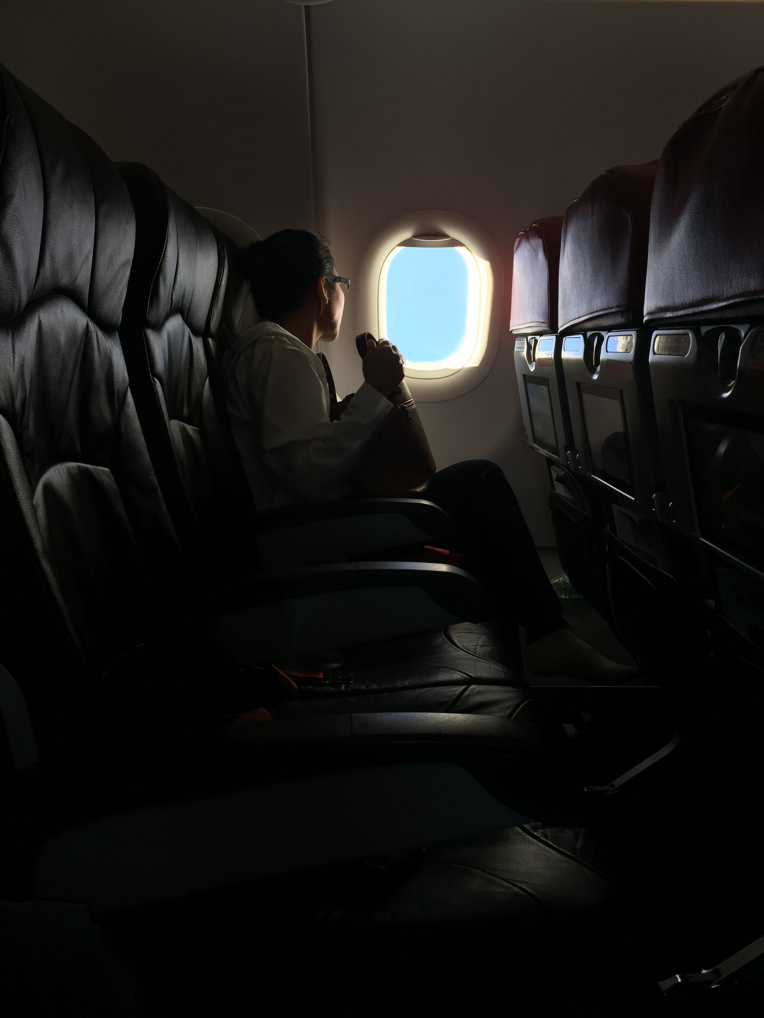 person sitting on plane watching the window