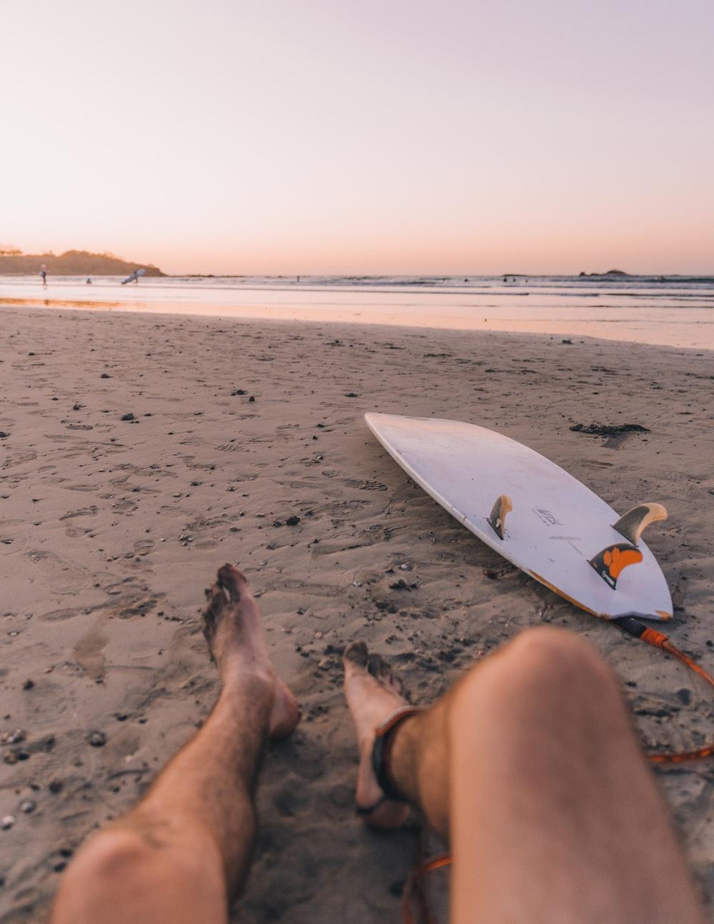 person sitting on seashore near surfboard in front sea