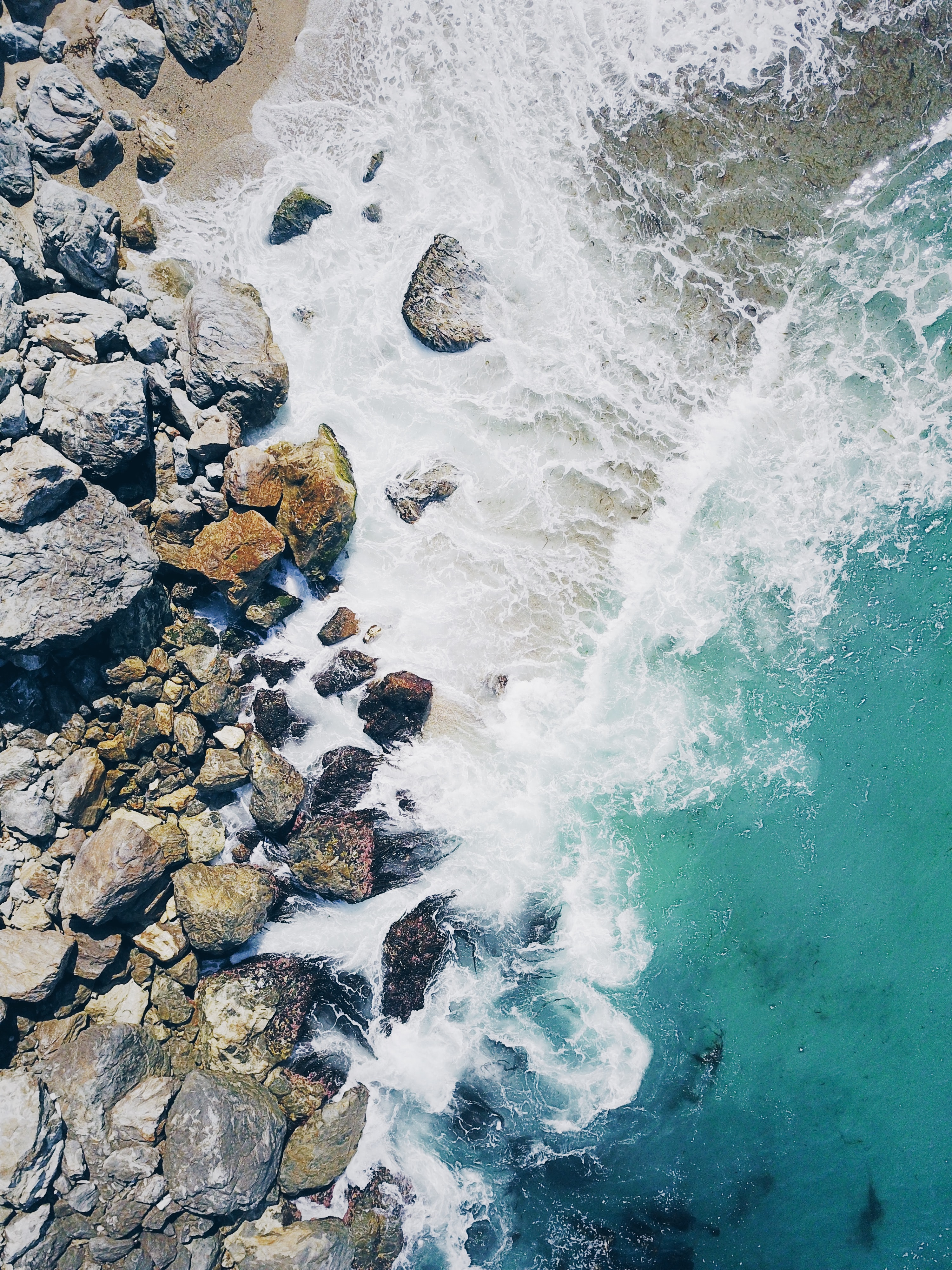 aerial view photography of sea waves near rocks