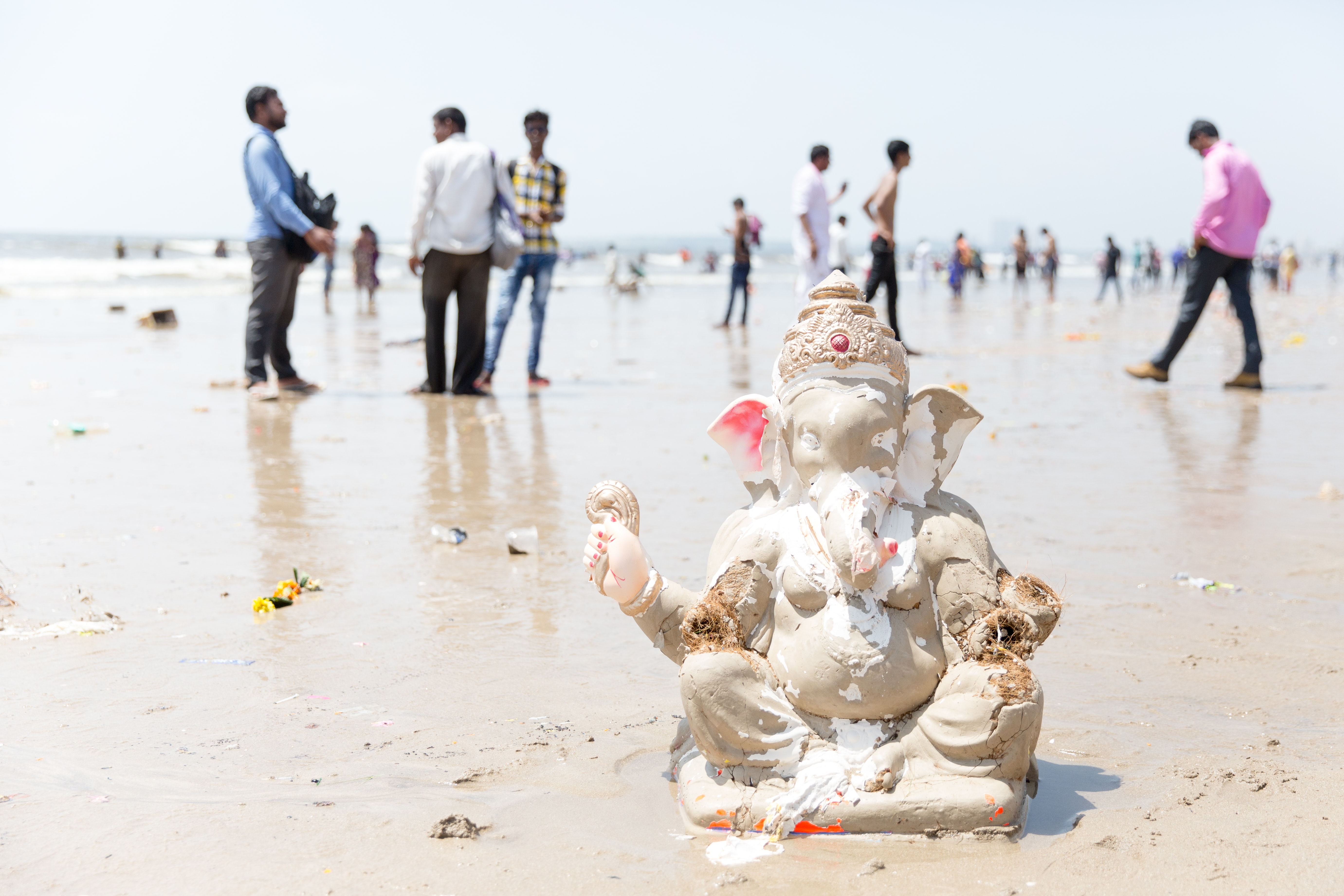 Lord Ganesh figurine on white sand near people during daytime
