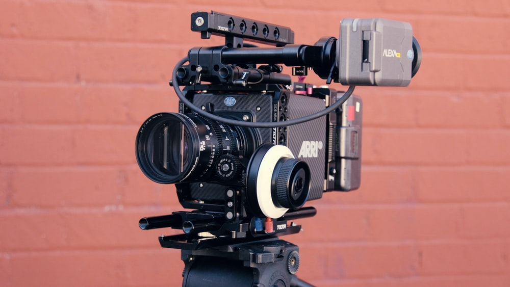 black Arri professional video camera in front of brown wall