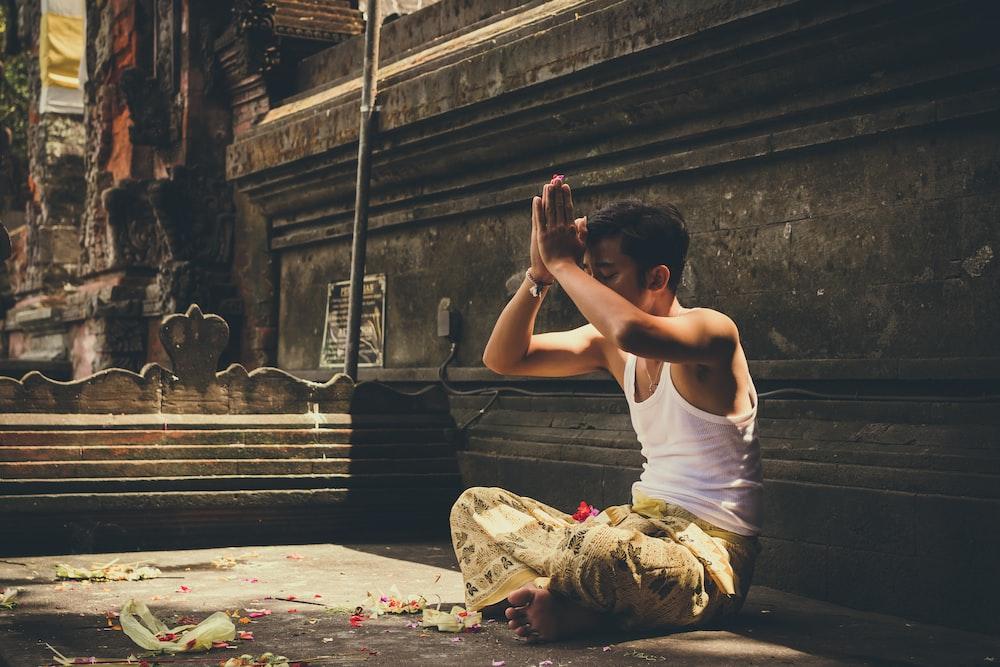 man in white tank top praying