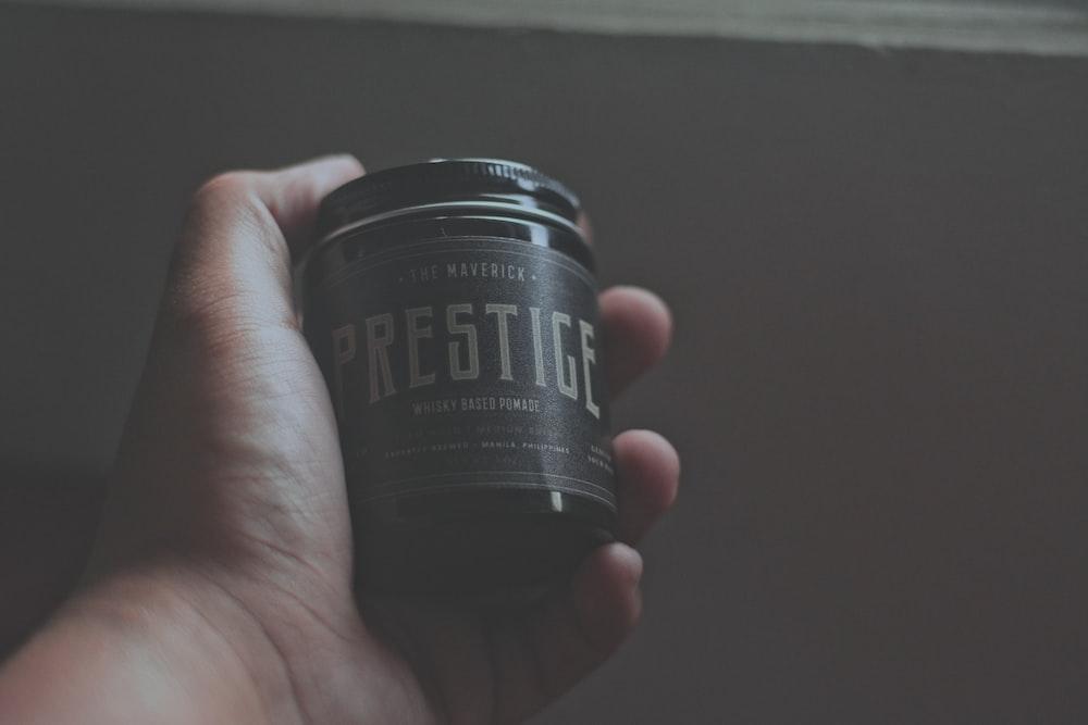 person holding Prestige bottle