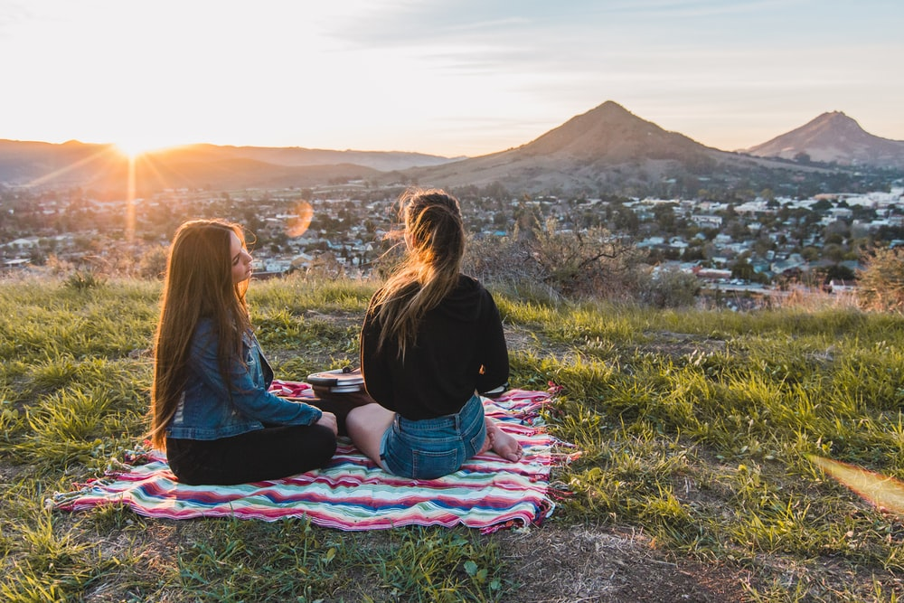 two women having picnic facing mountain and buildings during golden hour