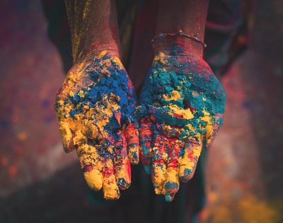 closeup photo of person holding color soils india teams background