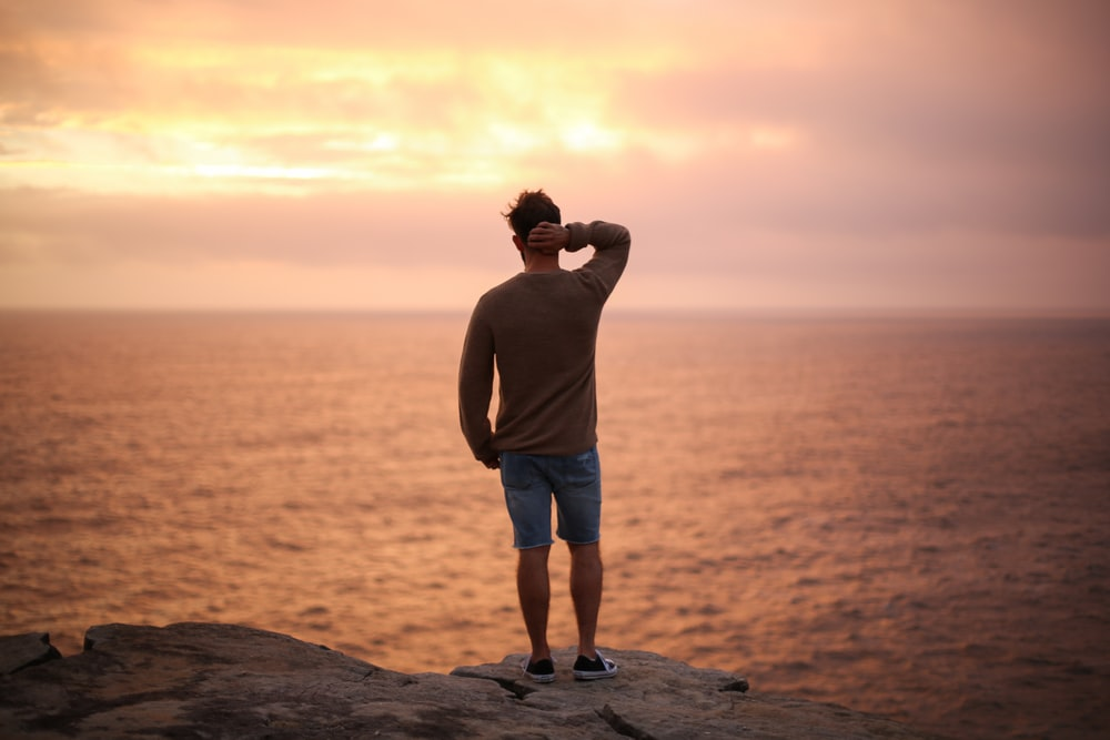 man standing on rock near seashore during sunset