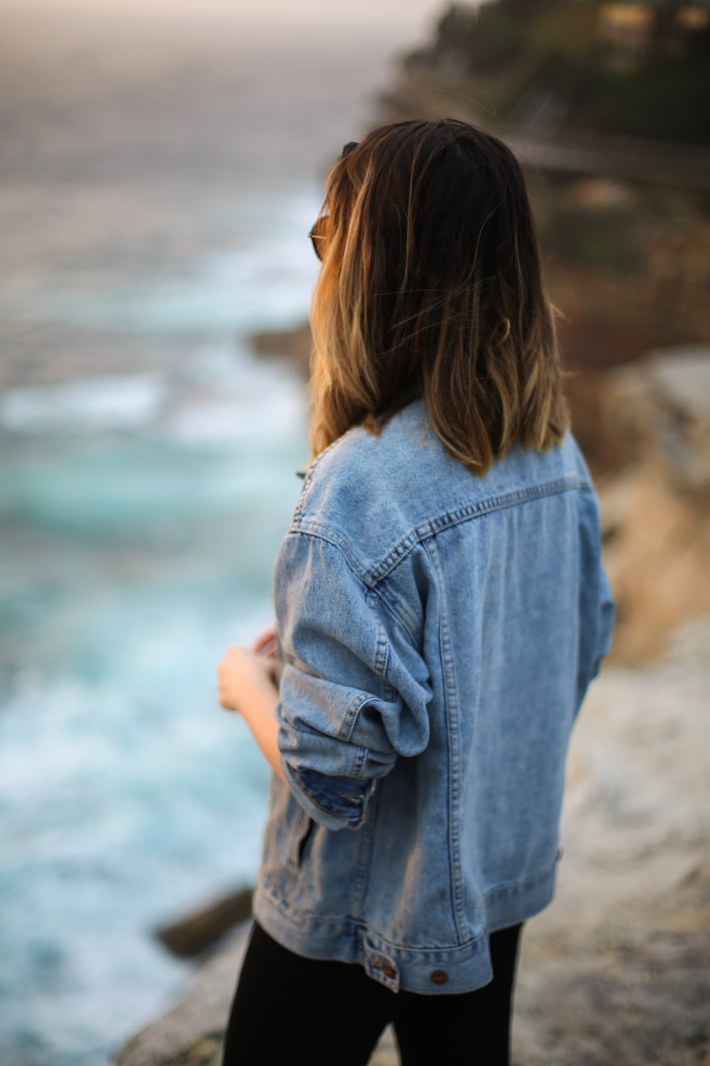 woman in blue denim jacket looking at the sea