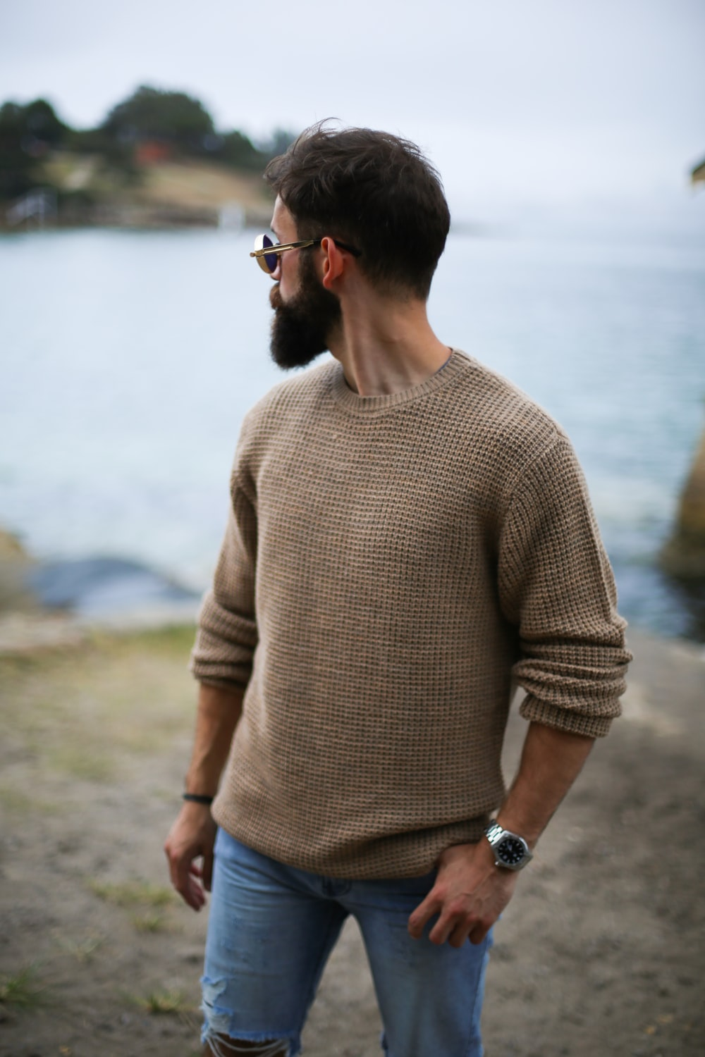 man in brown knitted sweater near beach