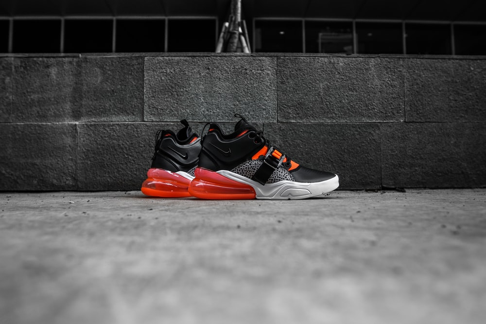 black-and-red Nike athletic shoes on gray floor
