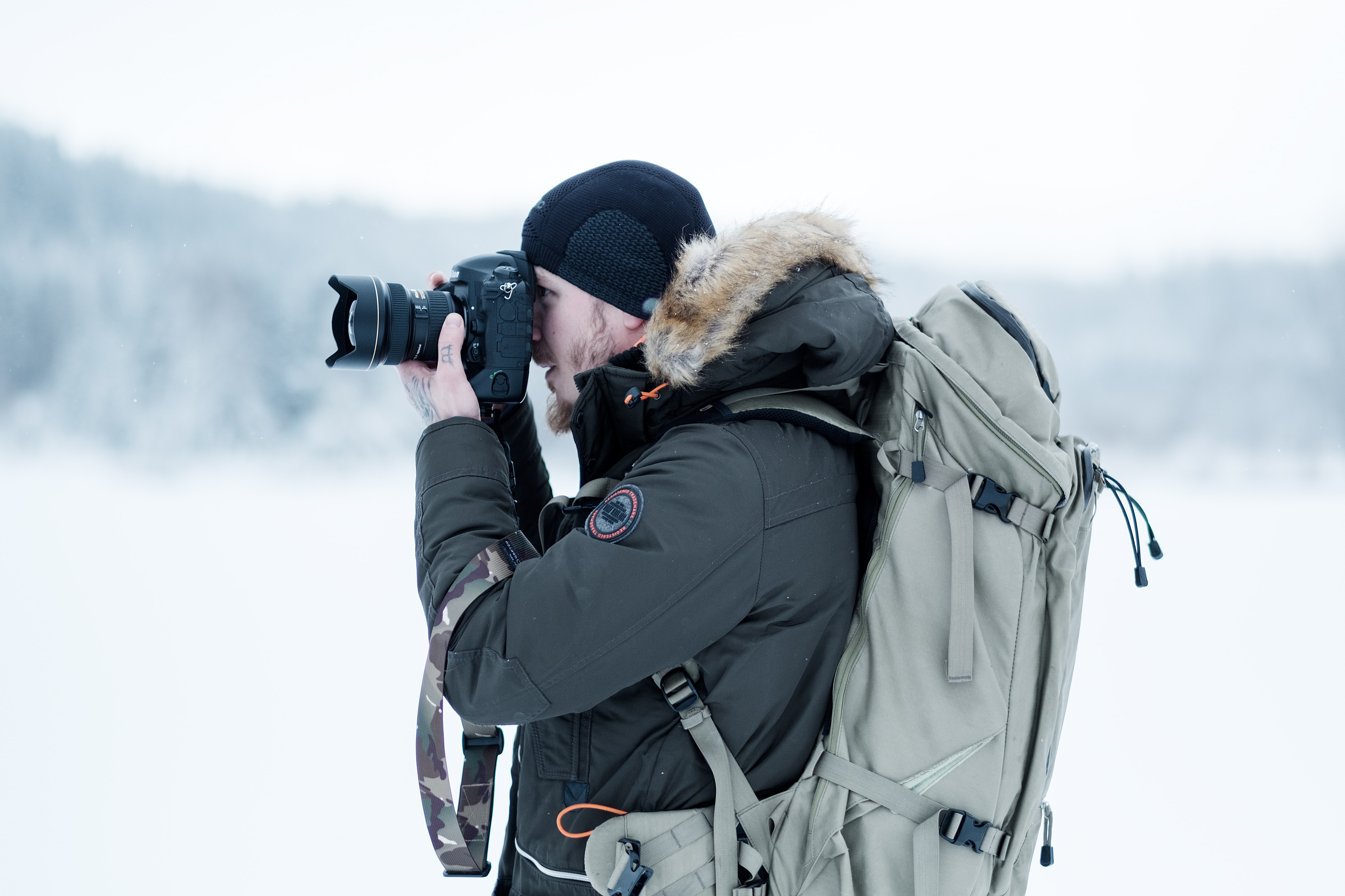 man standing on snow field while taking photo