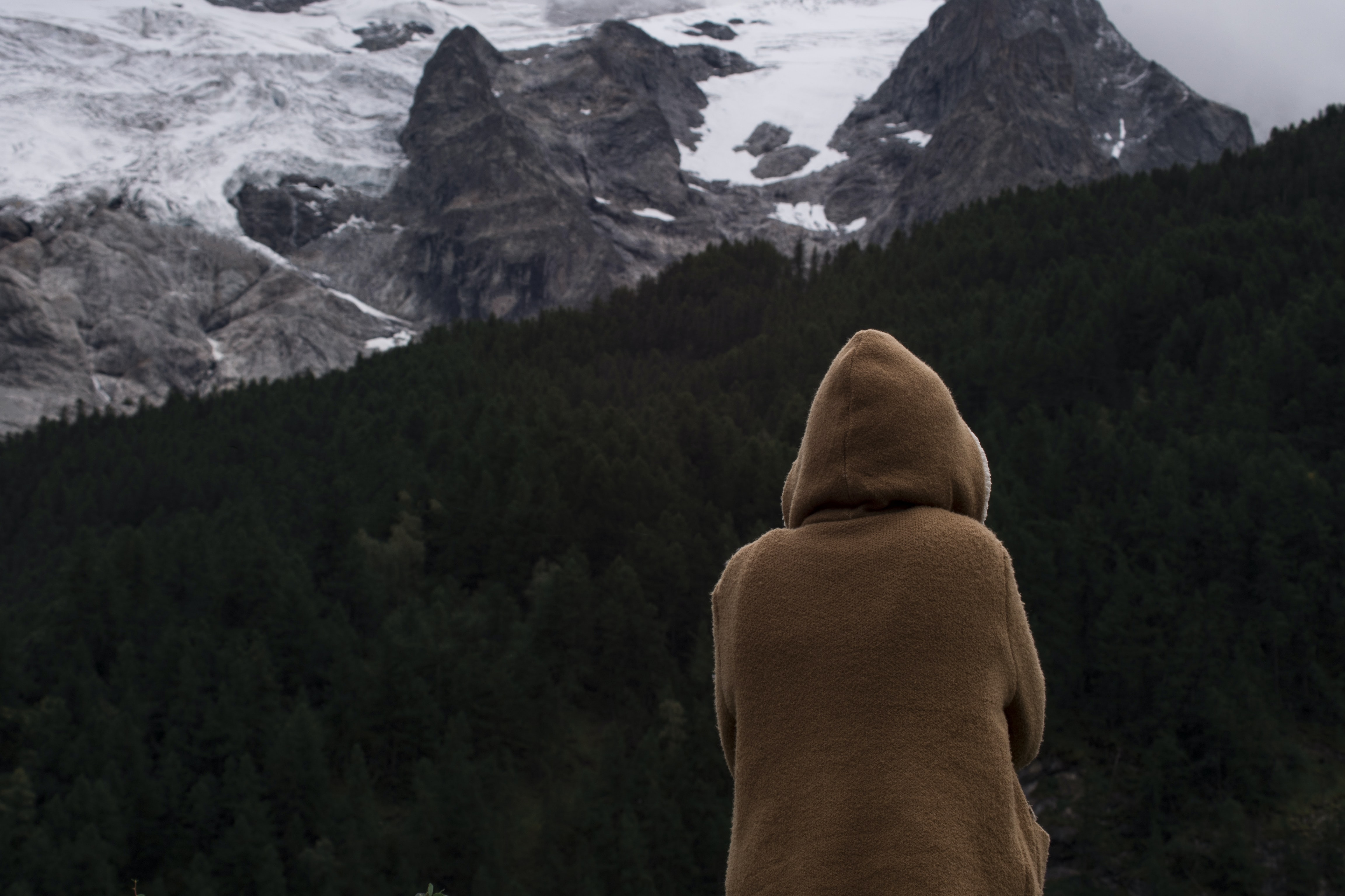 woman wearing hoodie sitting against mountains