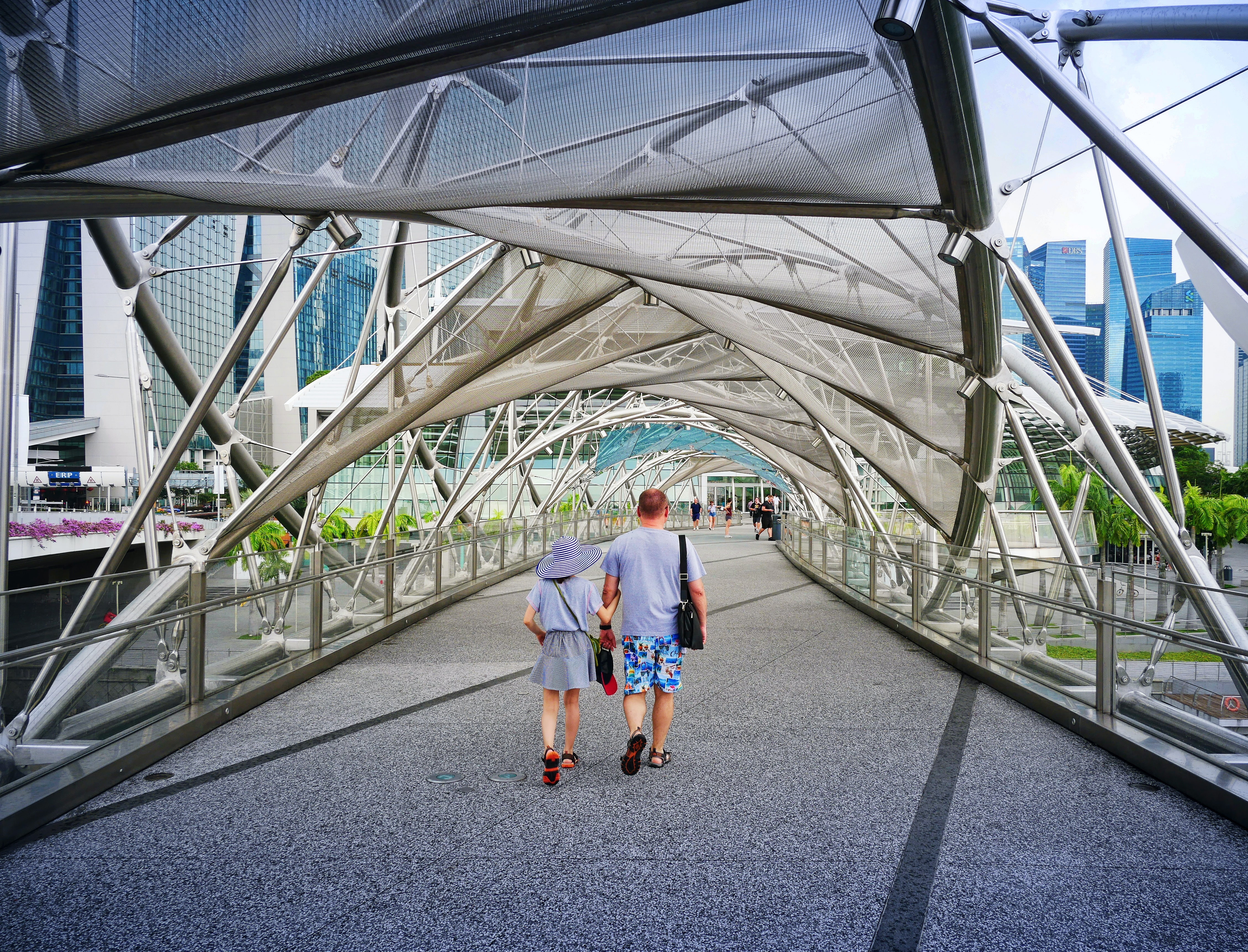 man and woman walking inside clear glass roof pathway at daytime