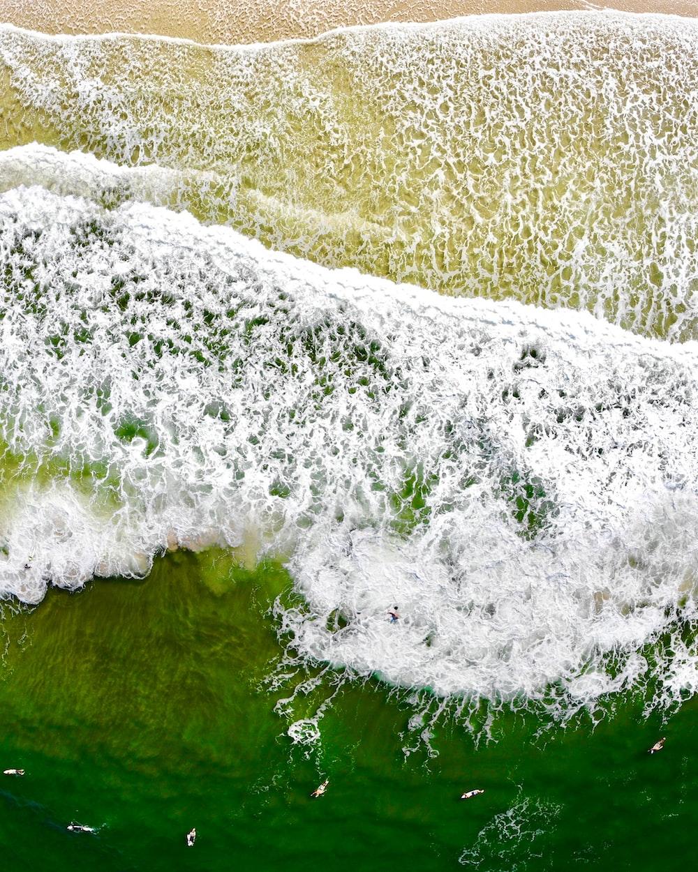 body of water waving on seashore
