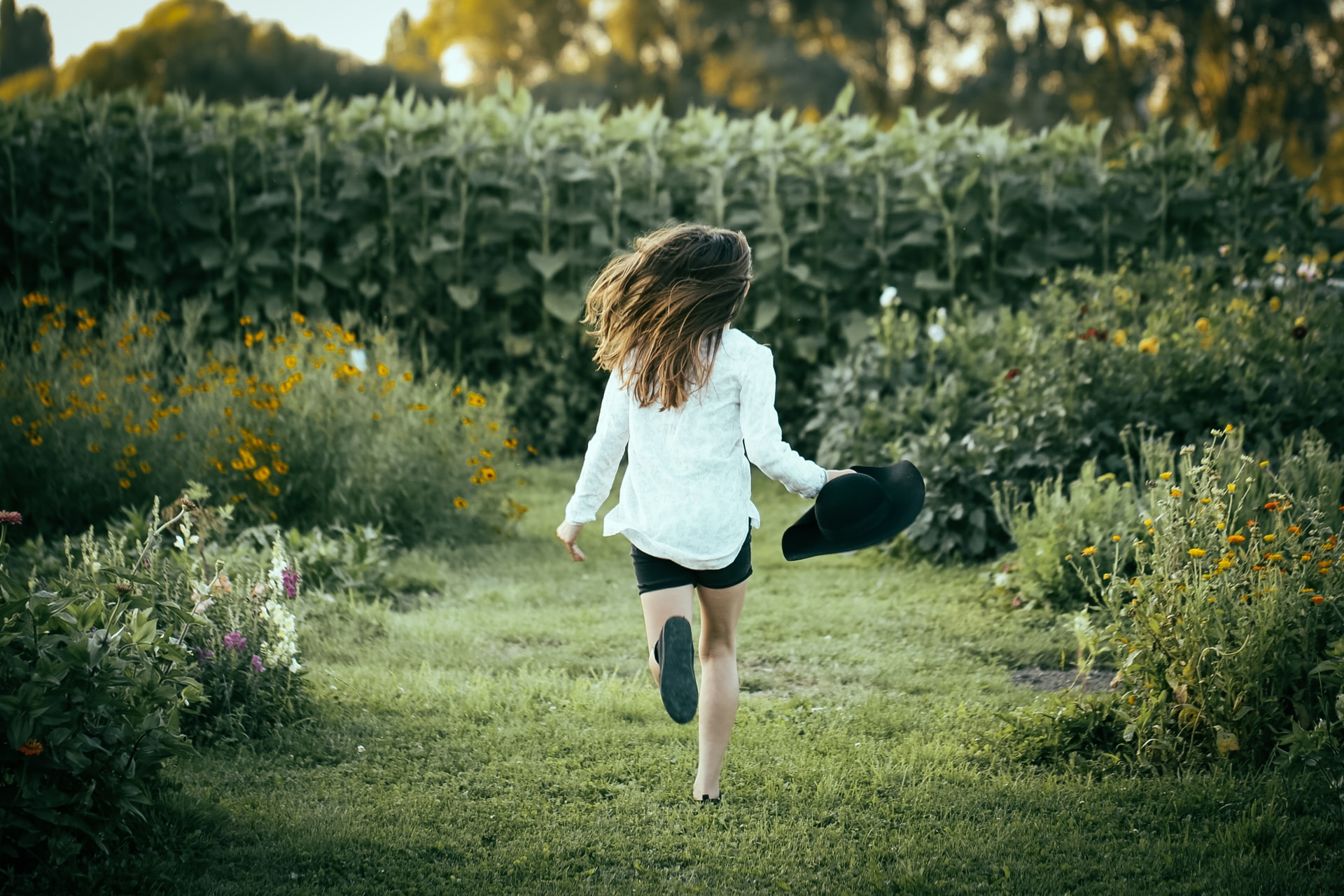 woman running on grass surrounded with flowers during daytime