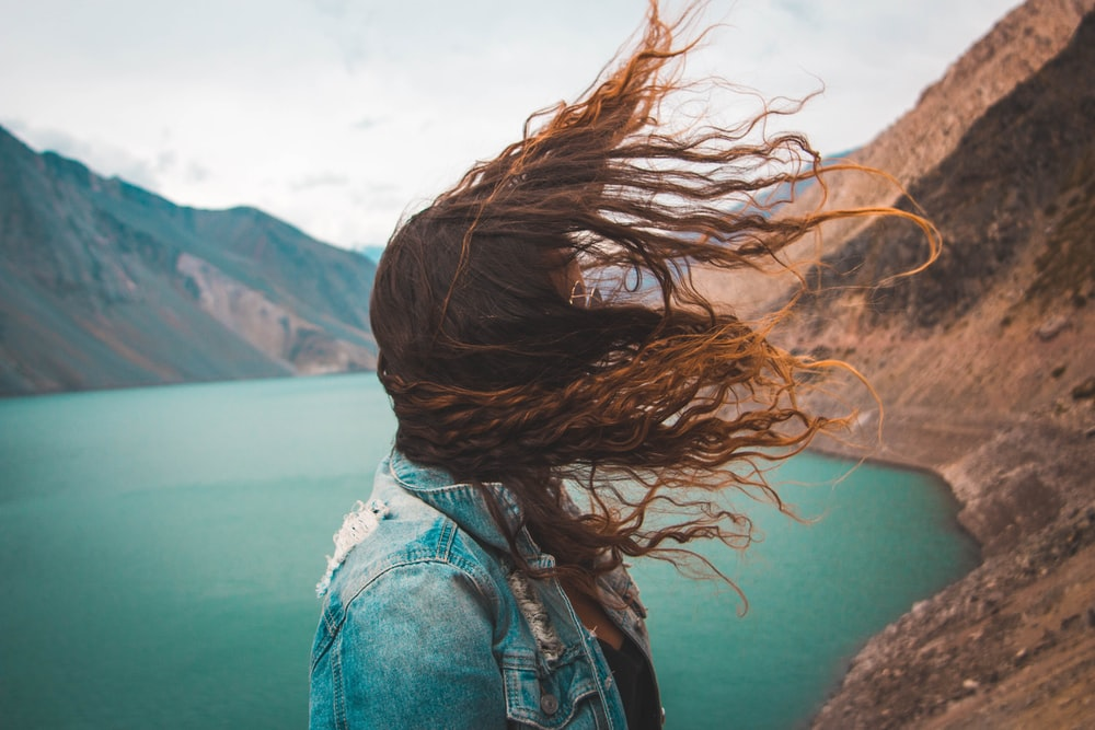 woman's hair covering her face near body of water