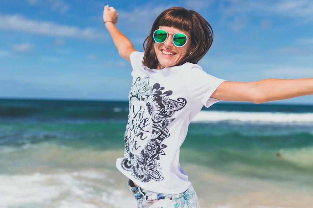 woman wearing white and black shirt jumping near seashore