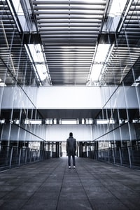 person standing near curtain wall building grayscale photography