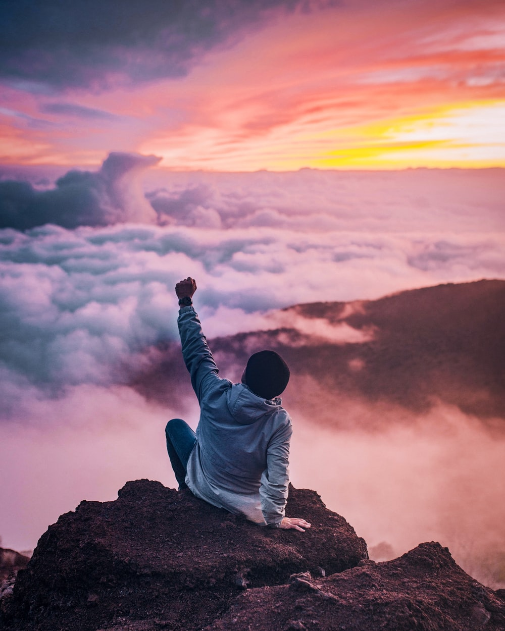 man sitting on mountain cliff facing white clouds rising one hand at golden hour