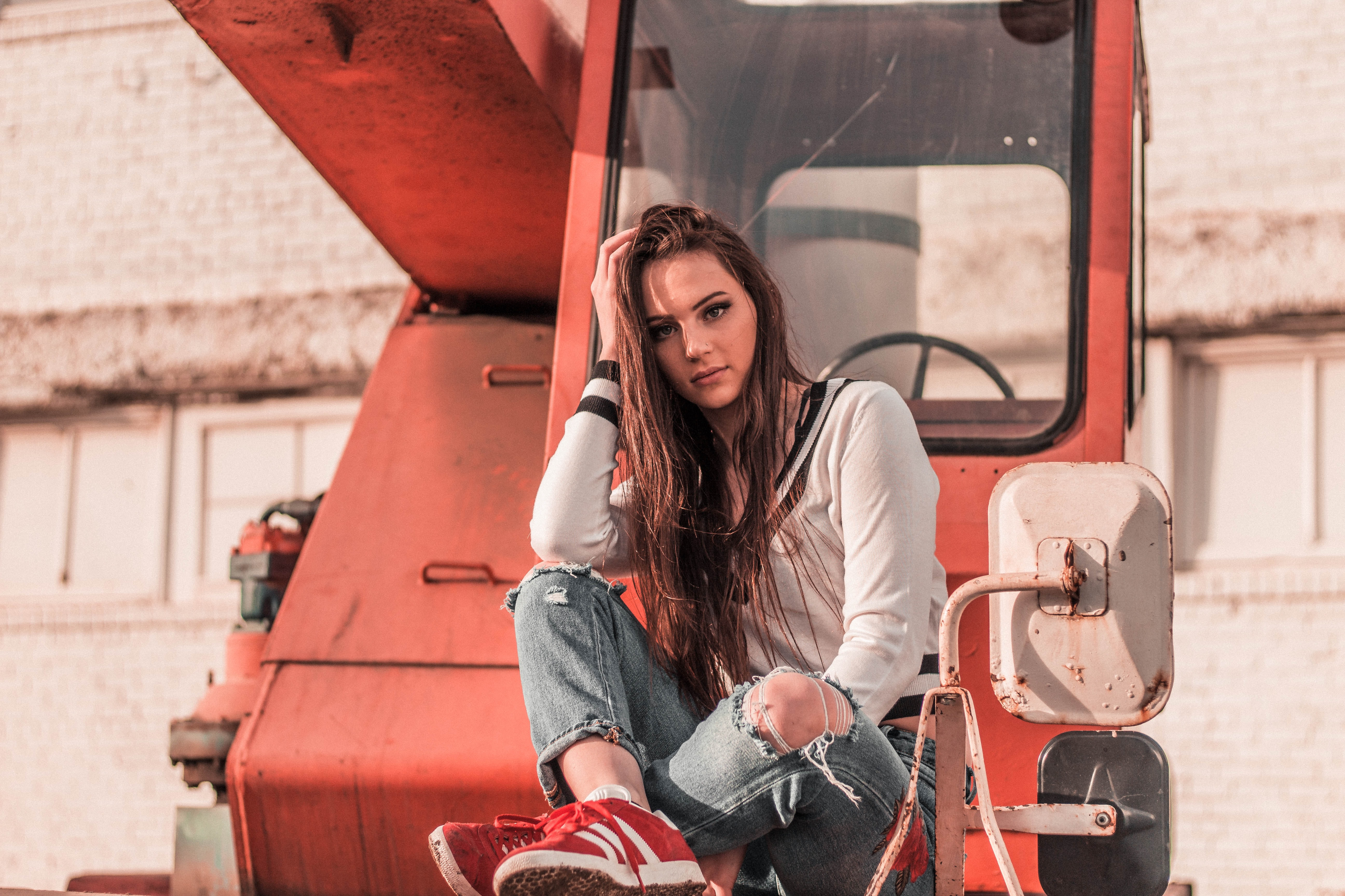 woman sitting in front of red heavy equipment while resting her hand on head