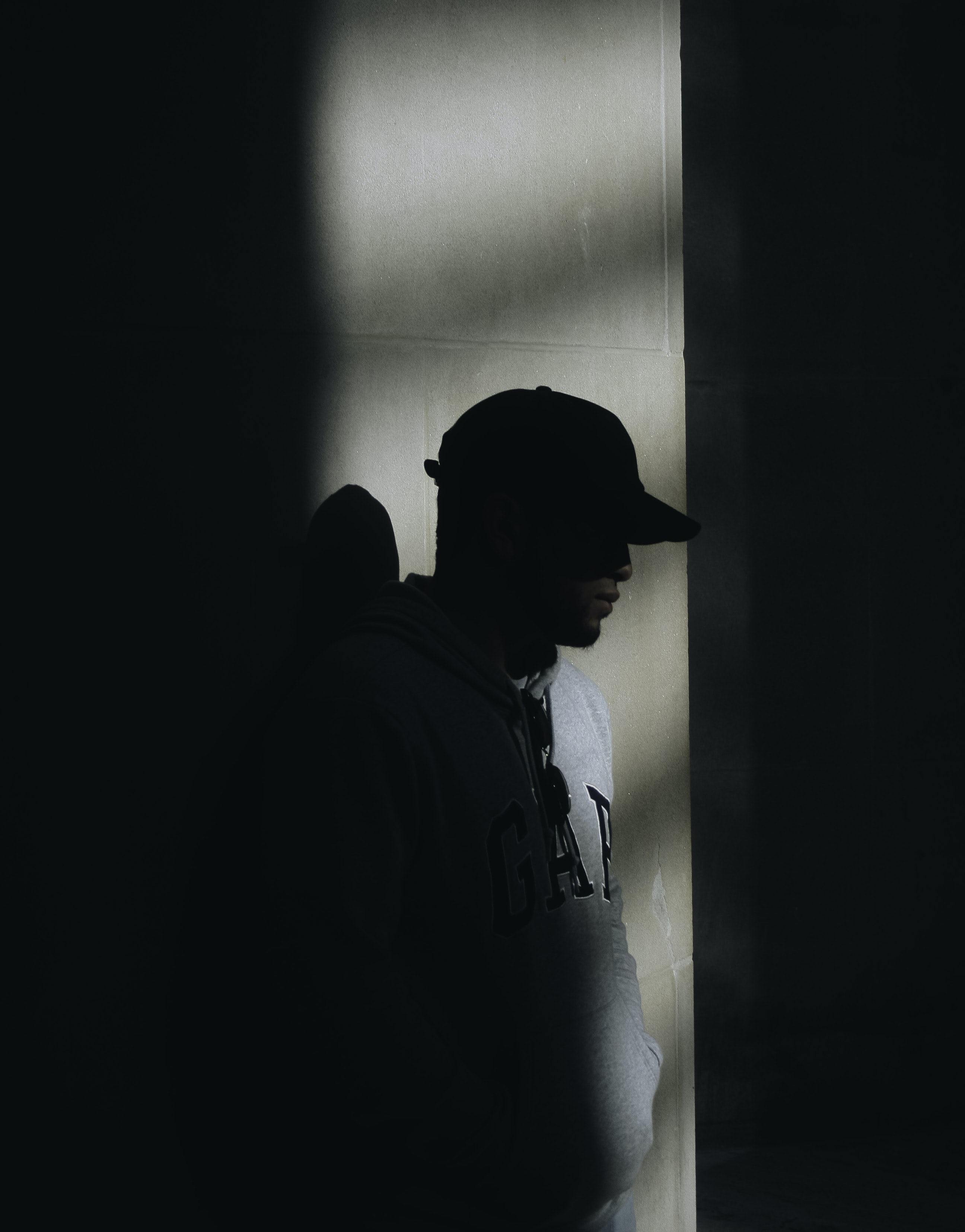 man in gray Gap hoodie standing on dark place