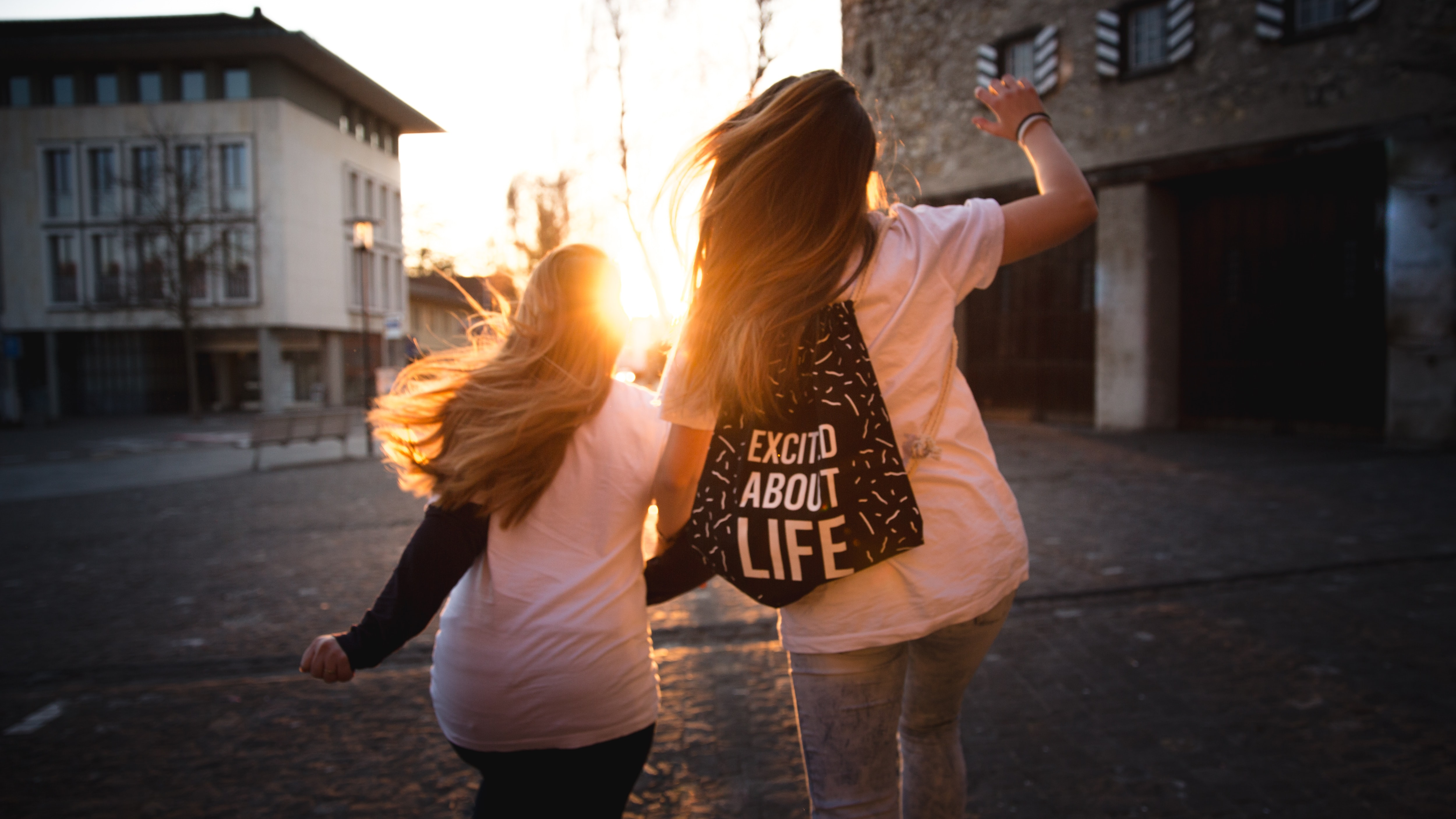 two women walking across the road during sunset