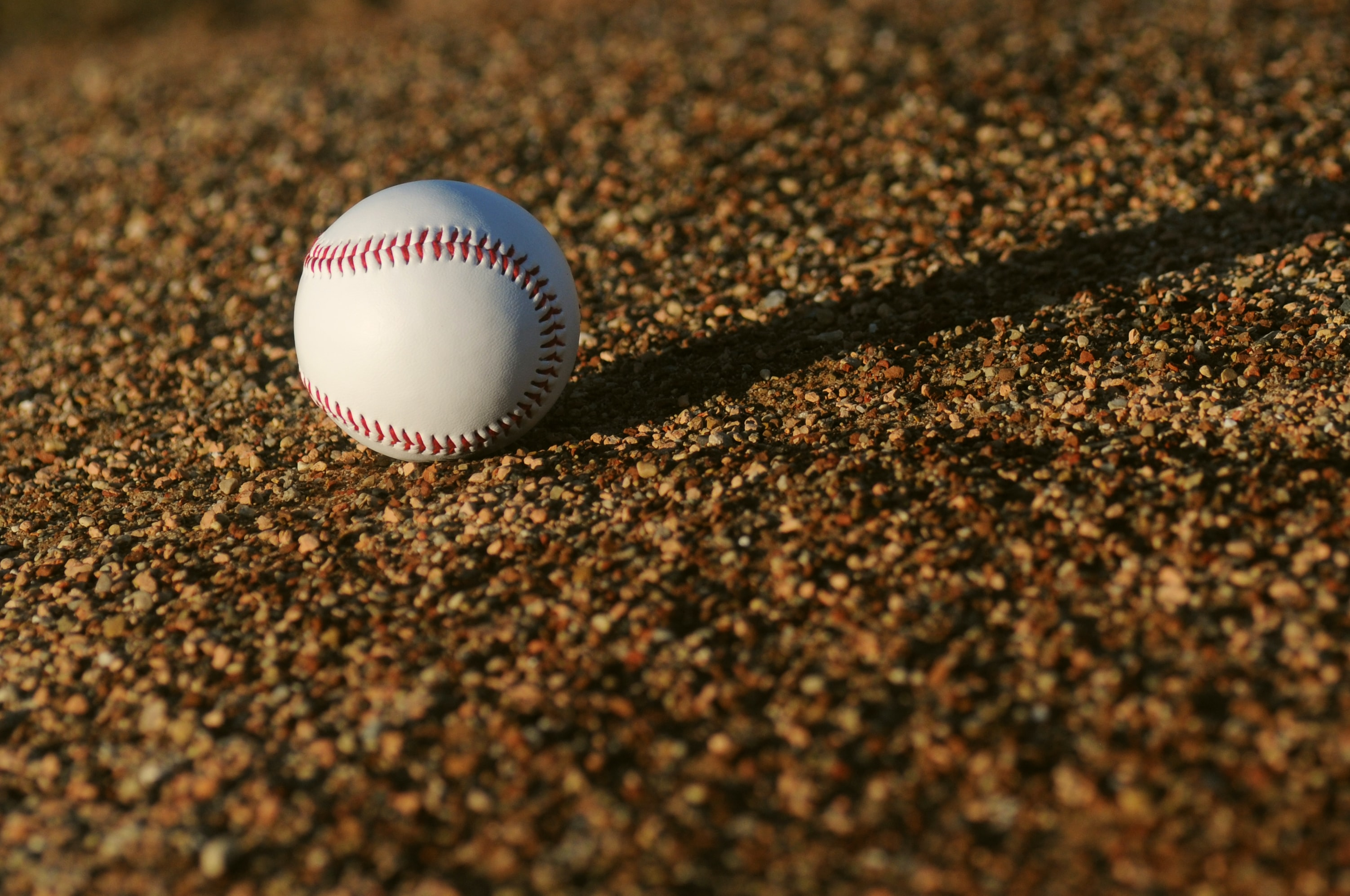 white and red baseball on brown soil at daytime