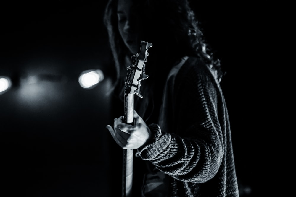 grayscale photography of person playing guitar
