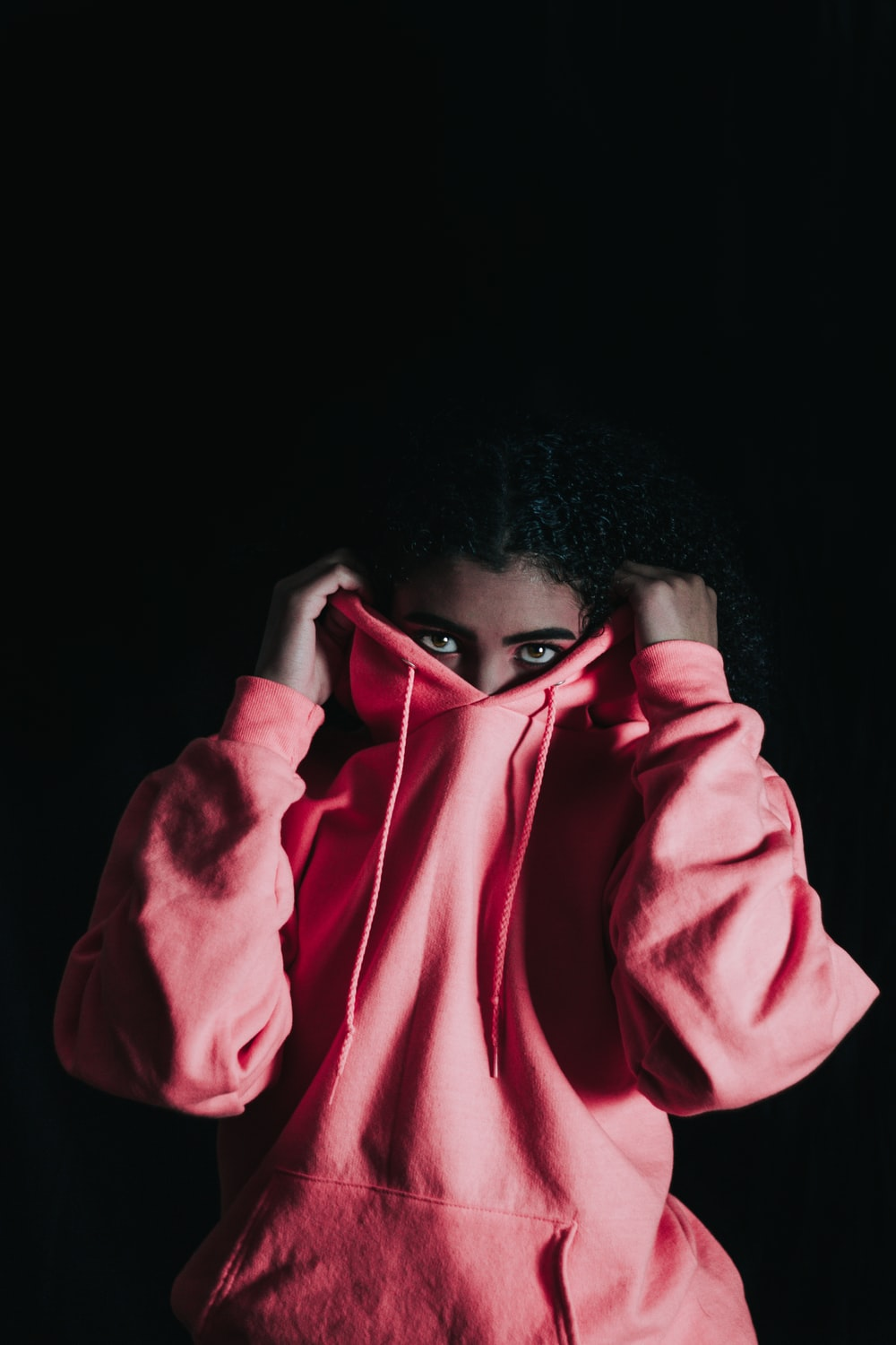 girl wearing pink pullover hoodie covering her nose