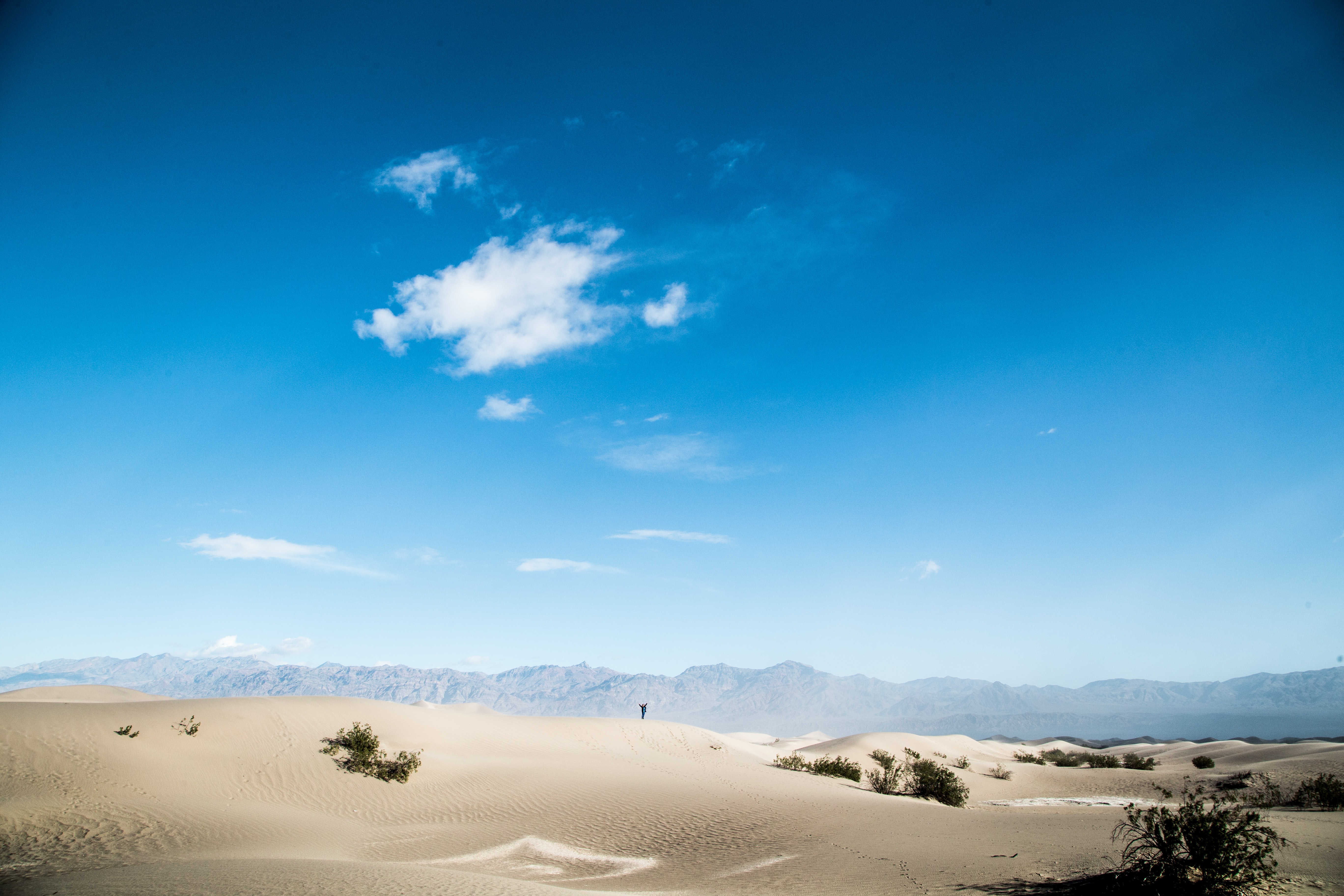 desert under blue sky and white clouds at daytime