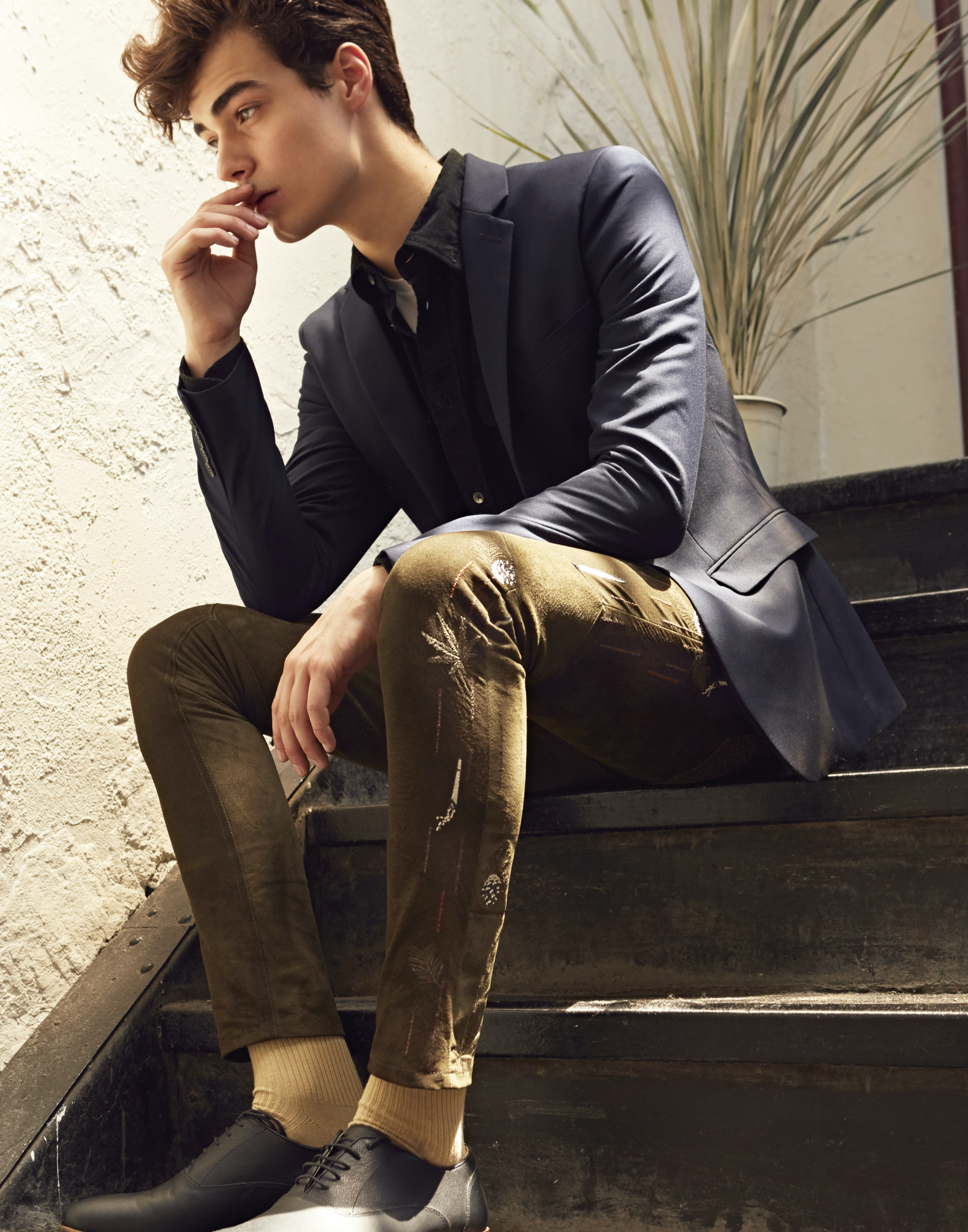 man sitting on brown staircase