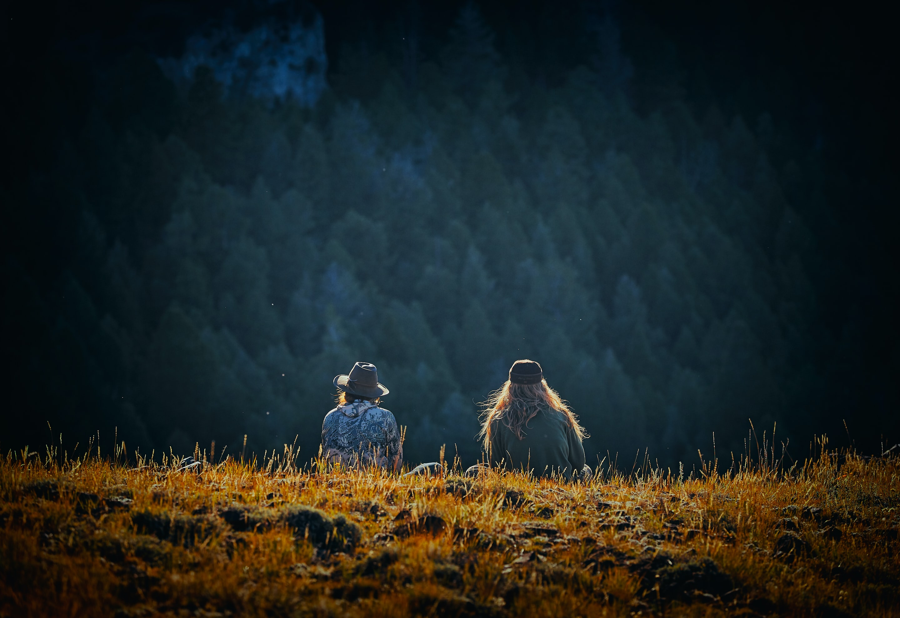 man and woman sitting on brown field