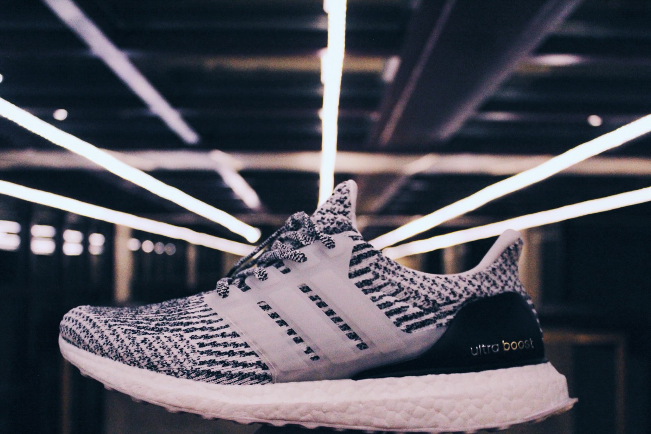 unpaired white and black adidas ultraBOOST shoe