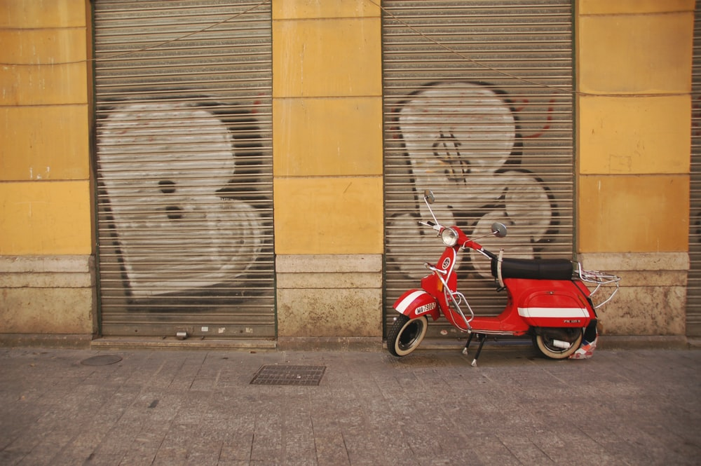 red moped beside gray rollup shutter