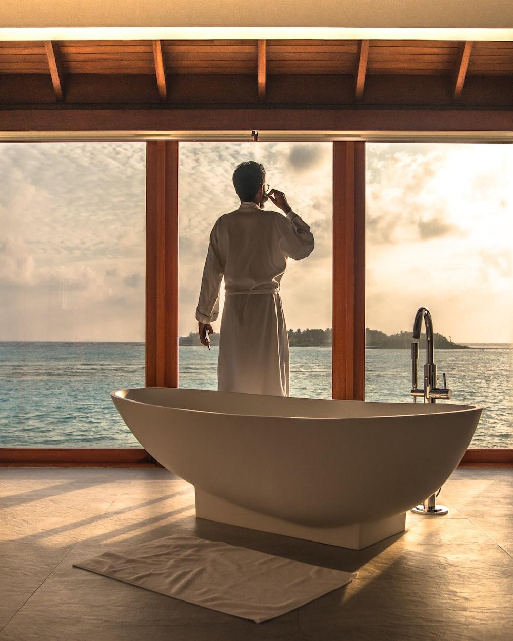 man standing beside bathtub