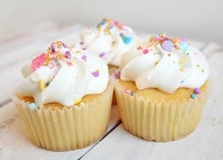 three cupcakes on white wood