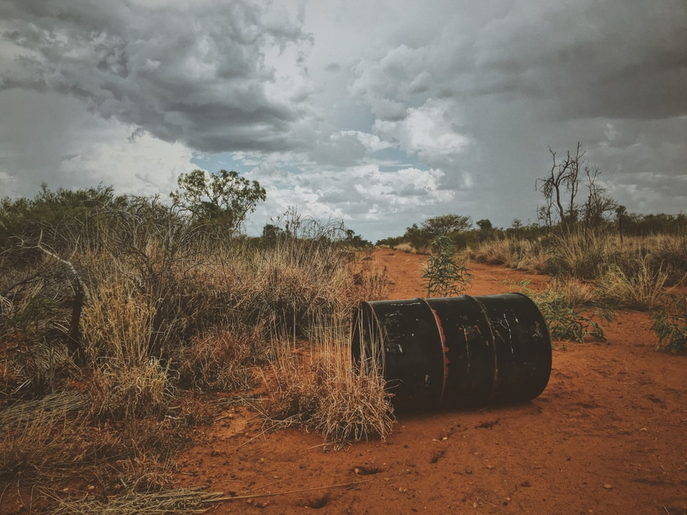 black steel container beside brown grass