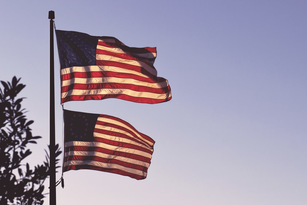 two flags of the U.S.A. on pole