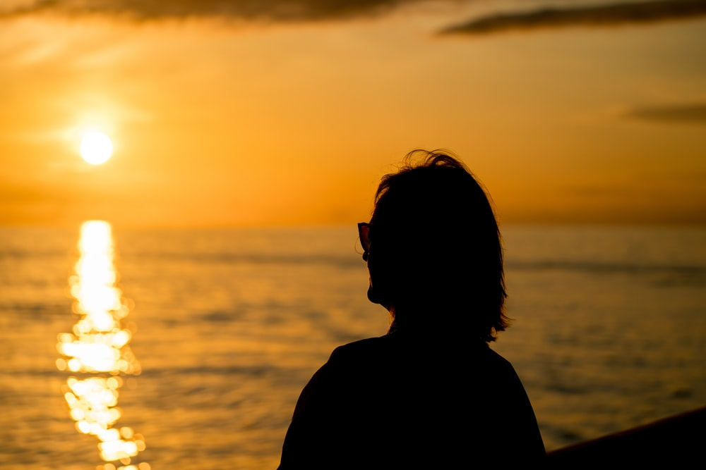 silhouette of woman standing facing sunset