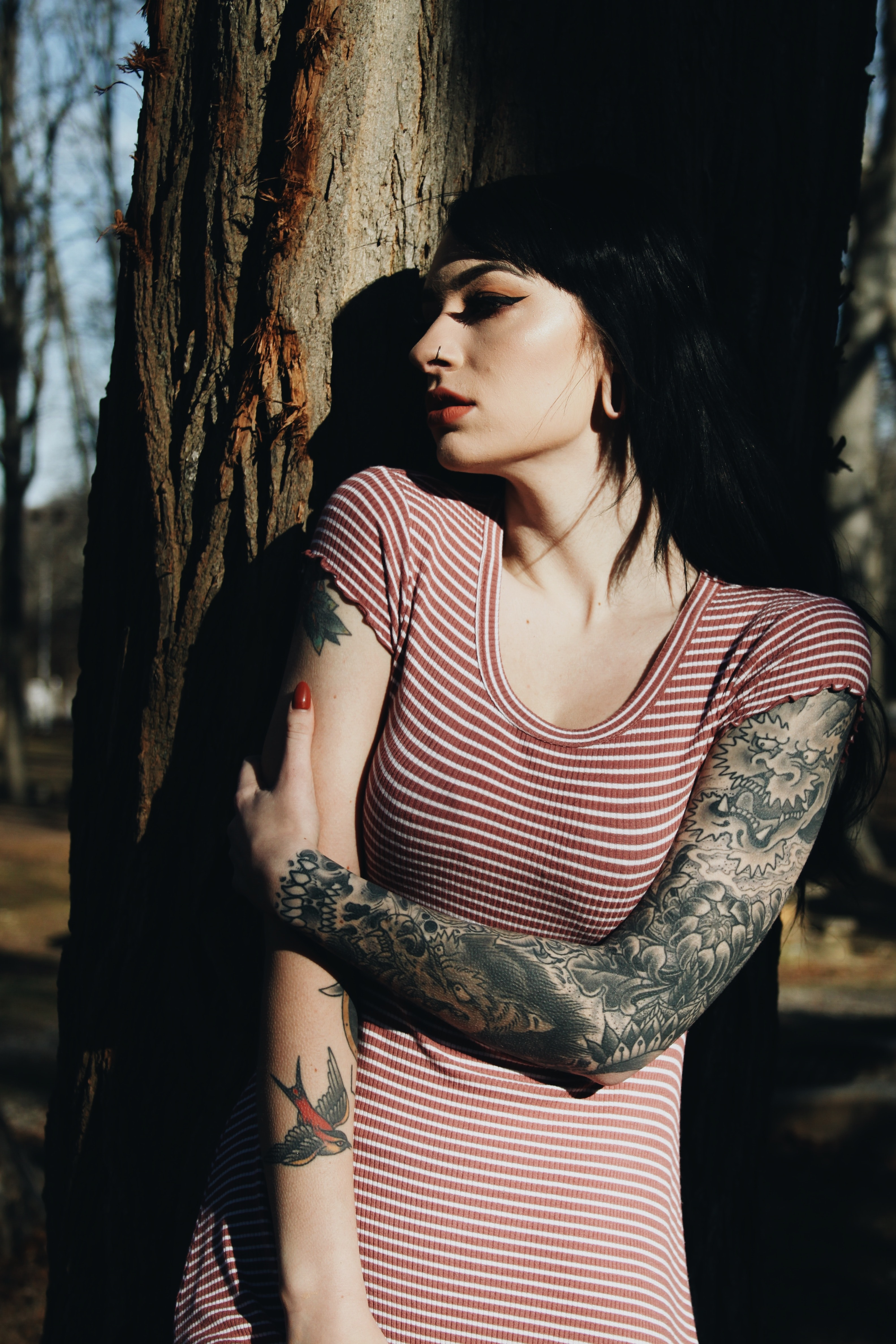 woman with dragon tattoo on left arm standing against tree
