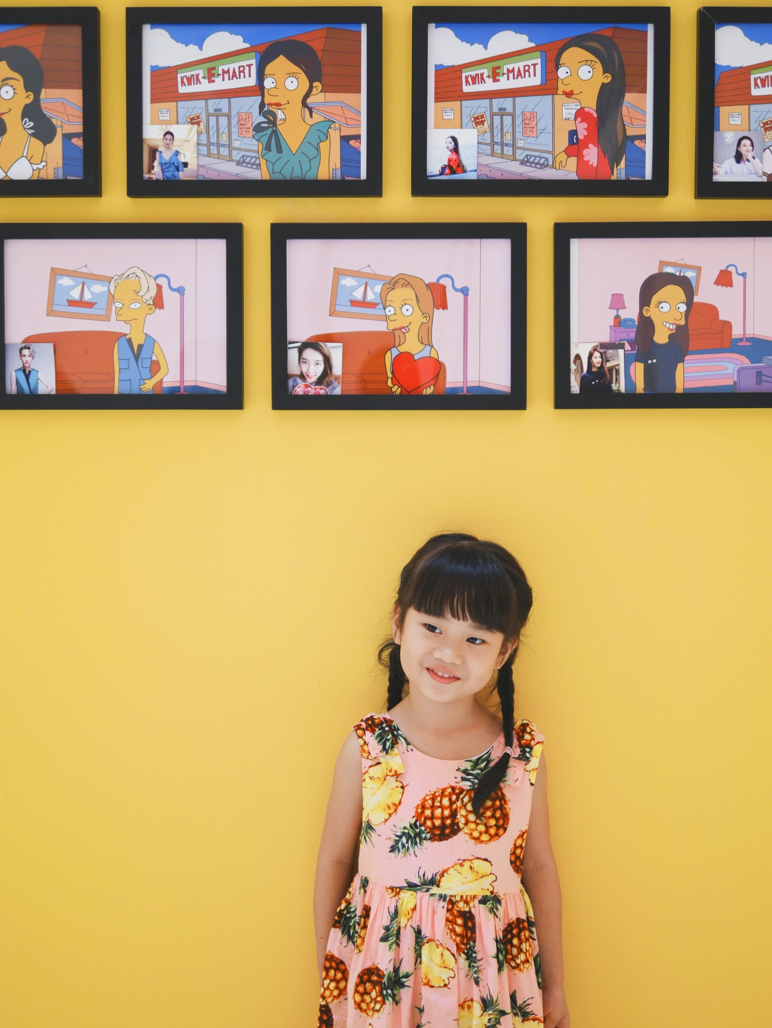 girl wearing pink and brown pineapple print sleeveless dress under E-Mart paintings