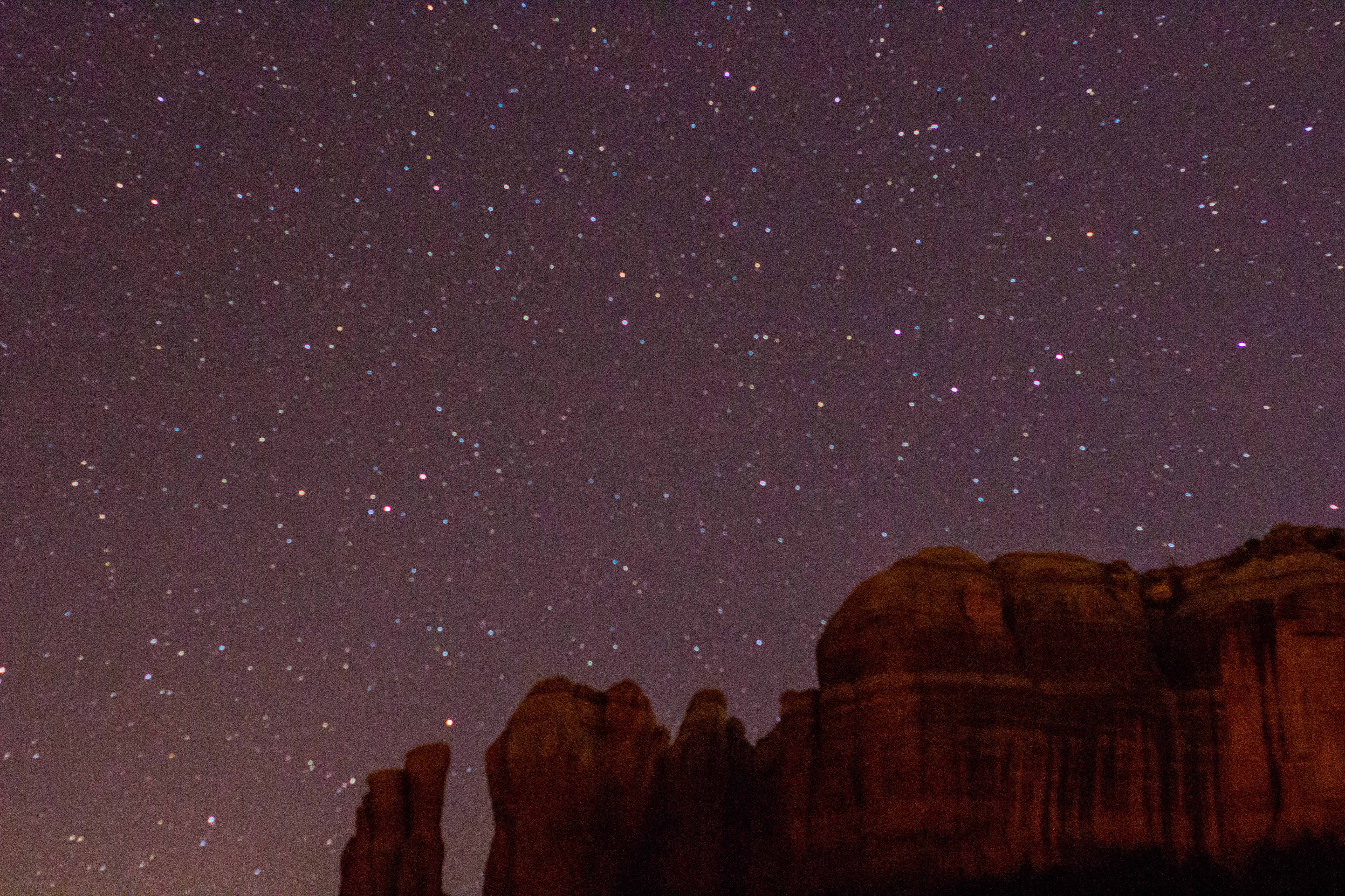 rock formation under gray sky with stars during night time